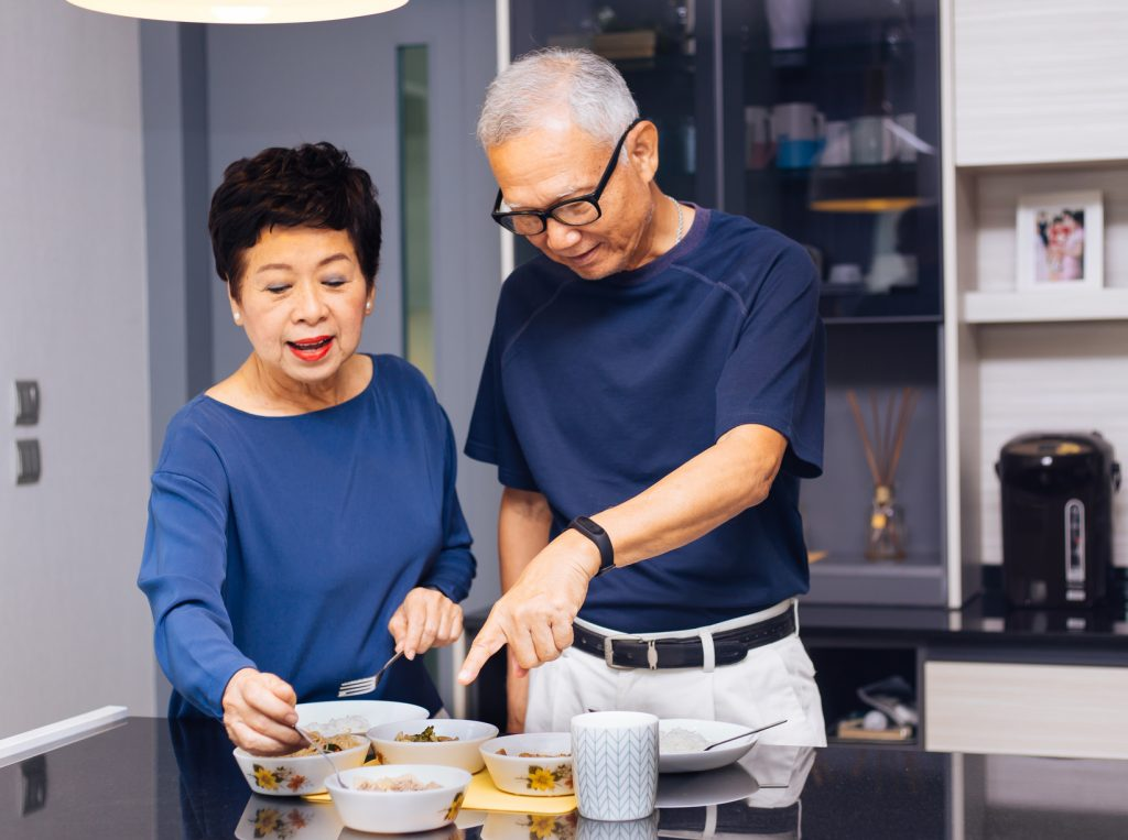 Senior Asian couple cooking together.