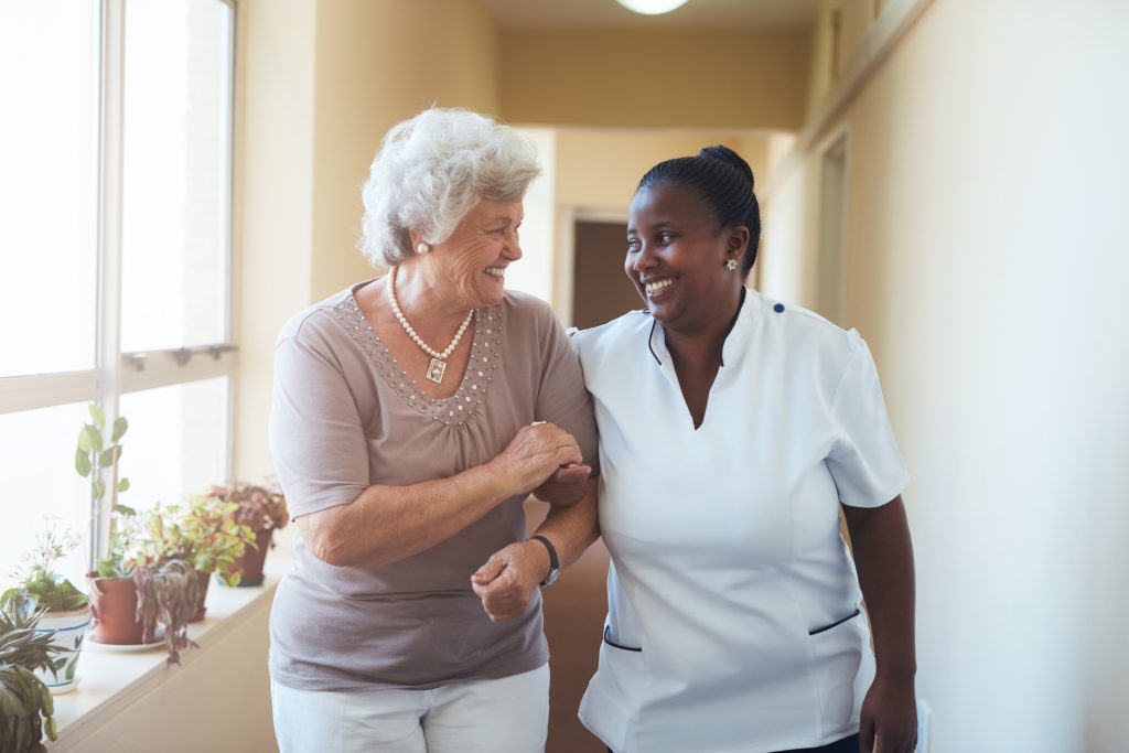 Older woman walking with nurse in residential senior care building