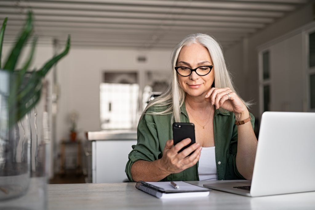 older woman smiles and looks at phone and open laptop