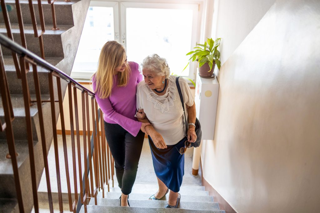 caregiver helps woman climb stairs