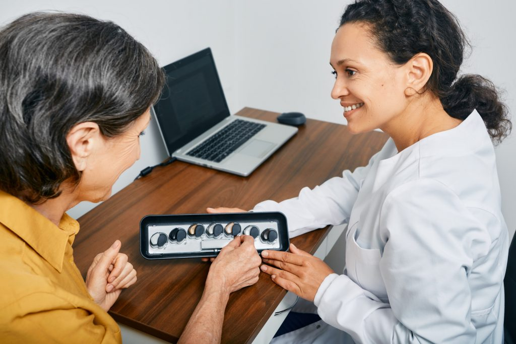audiologist presenting adult with hearing aid options